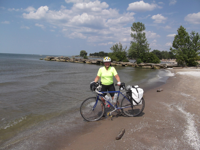 Mary and her Surly LHT tire dipping in Lake Erie at Edgewater Park in Cleveland Ohio after riding 350 milesThe Ohio to Erie Trail