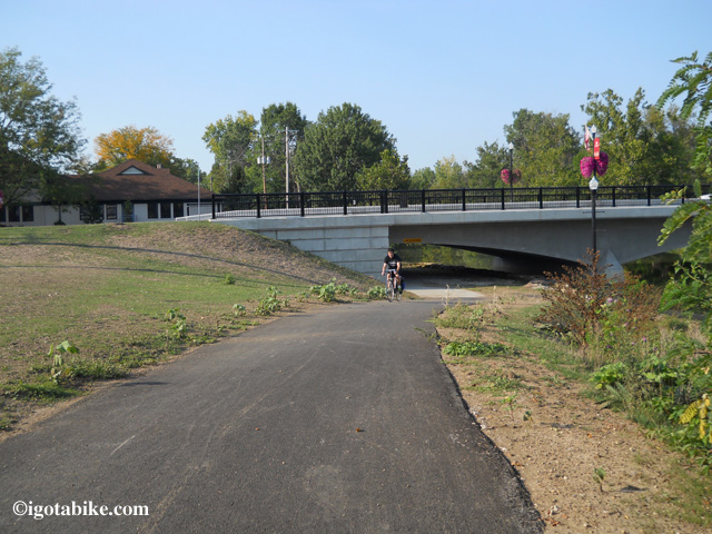 This photo shows the Main Street bridge with a bike trail going under the bridge where it dead ends into the parking lot behind the Senior Center. Stay up on top and go forward on the bike bath (out of view, left) up to Main Street to turn left.